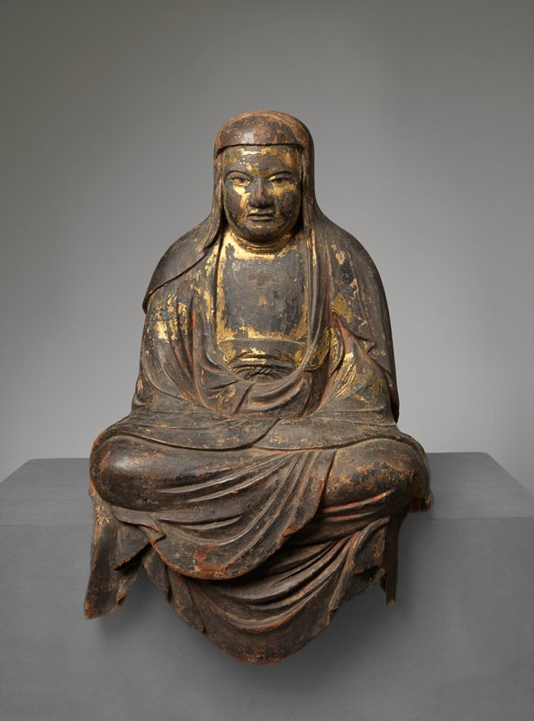 seated figure with legs crossed, hands clasped on lap; shroud over head draping over shoulders; clothing drapes over front knees; remnants of gold pigment; inlaid eyes