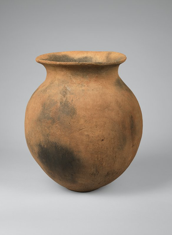simple vessel with round, bulbous body, gentle neck, flaring, wide mouth; natural brown color with dark spots from firing; round bottom, does not sit evenly