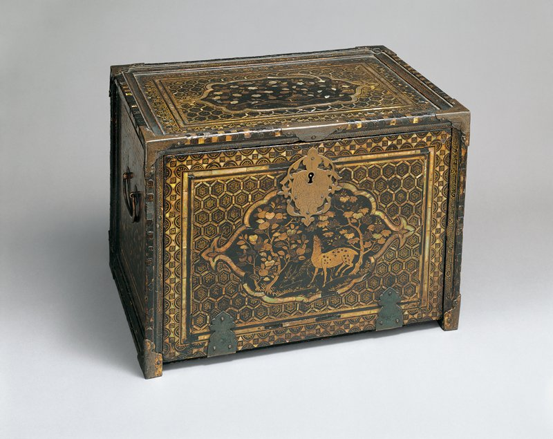 black lacquered chest with ornate mother of pearl inlay; nature scenes on side panels, with trees, grasses, deer on front; drop-down front panel; seven small drawers inside with grasses, flowers, birds, rivers; drawer at center with archway and keyhole, featuring two fish swimming among seaweed