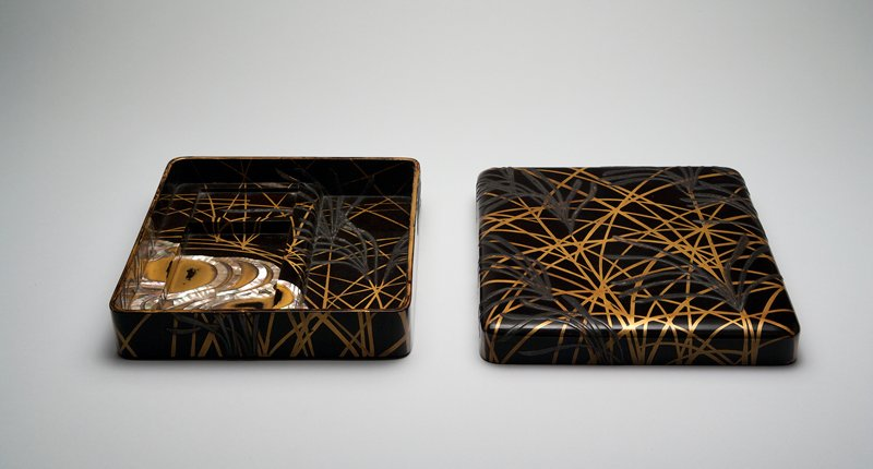square writing box with exterior design of gold and lead overlapping reeds; inside stylized gold stream in corer with mother-of-pearl inlay designs representing current; gold and lead reeds continued inside