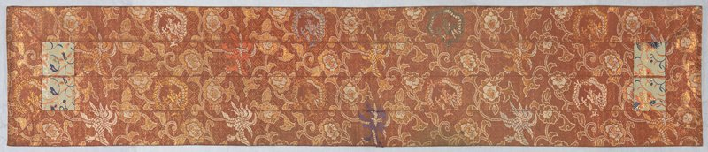 salmon-colored, brocaded silk with designs of dragons, phoenixes and floral motifs; two blocks of white brocade with blue and tan floral designs on each end