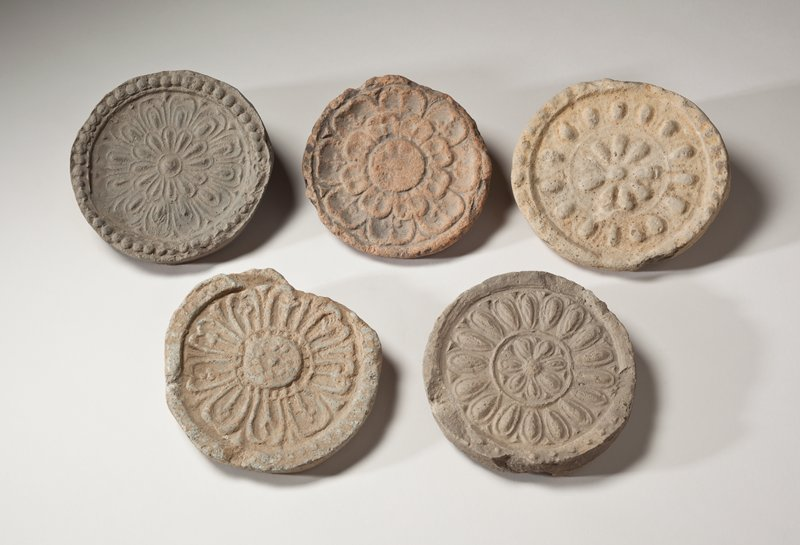 round roof tile end with stylized floral decoration; simple flower with raised petals at center surrounded by low round rib, and raised knobs on outer ring; light brown color