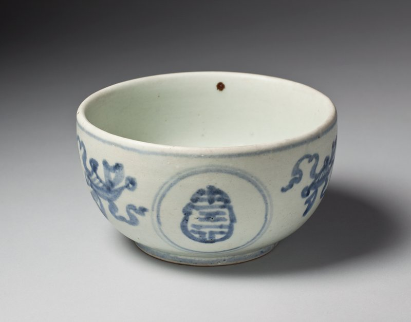 whitish bowl with blue underglaze motifs; abstracted, scrolling, ribbon-like designs alternating with stylized characters within double circles; stylized character inside outlined with two blue circles