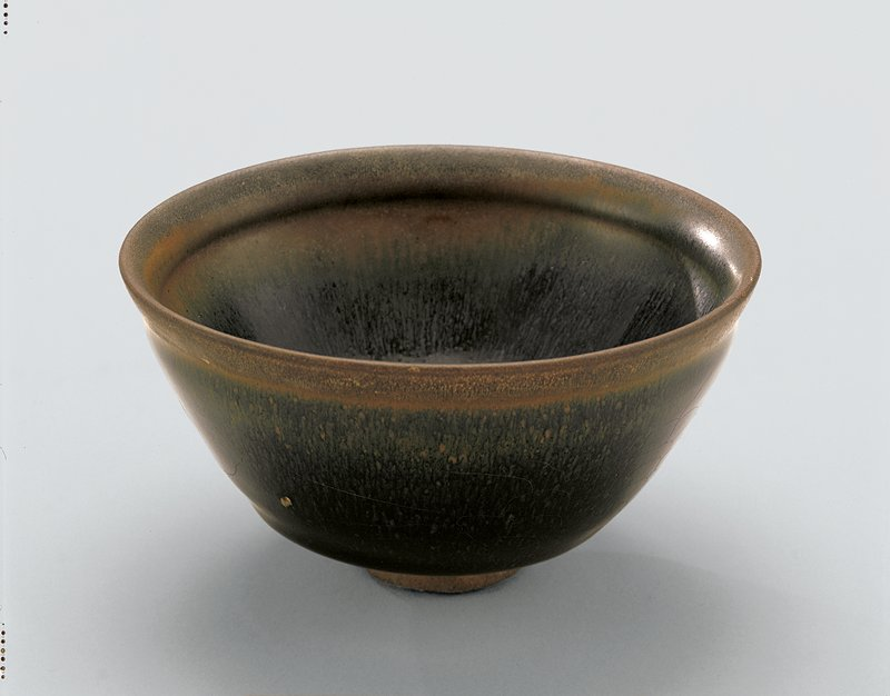 small bowl on very small foot; dark, somewhat mottled navy blue glaze with ochre, tan, and greenish gradients; lip is brown and rust colored; slightly raised scaly pattern around outside