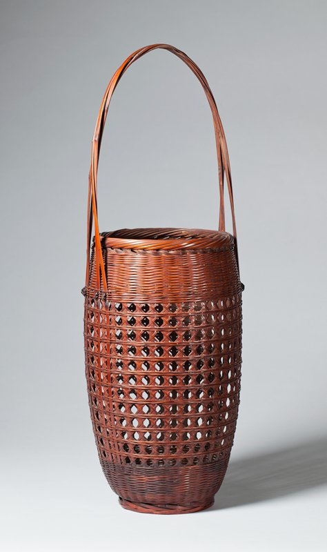 oval basket with open weave around most of body in diamond pattern; horizontal bands of closed weave around top and bottom; diagonal weaving around mouth; handle made of four thin reeds coupled together and crossed at top