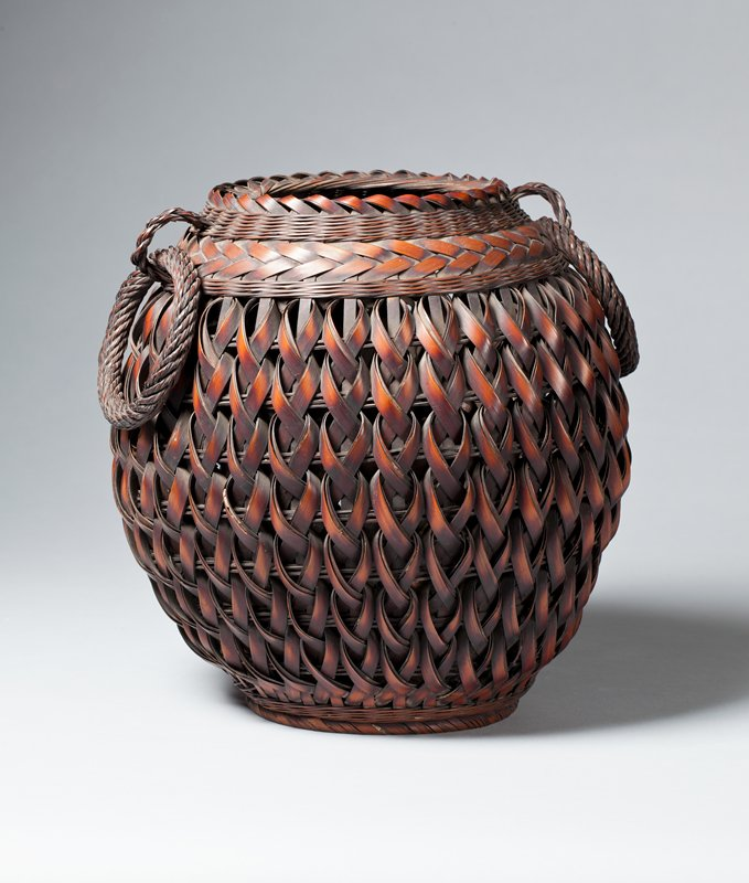 round basket with vertical weave in a series of braids; reddish brown hue; two large hoop handles on each side; basket narrows at base and underside is concave; metal insert