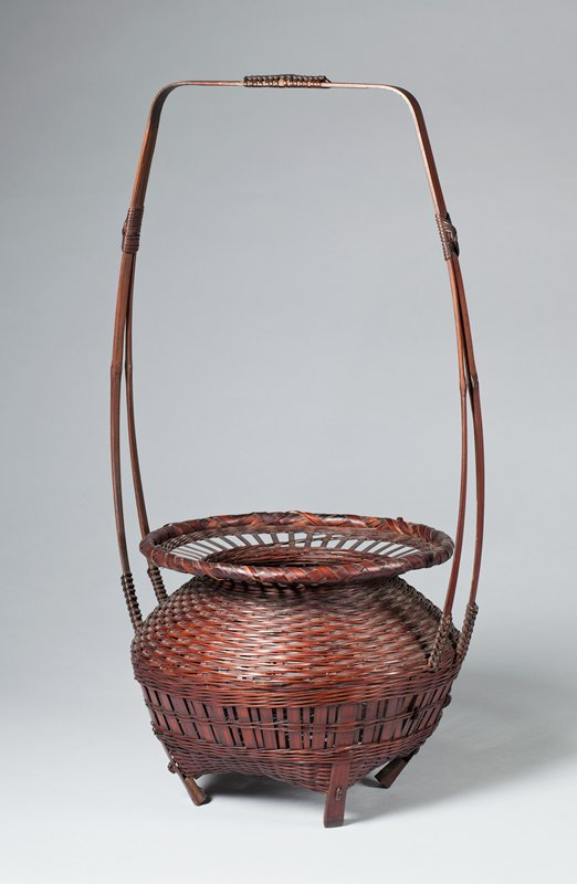 round basket standing on four inward pointing feet; slightly square around bottom; round body tapers inward at neck and then flares outward to a wide, flat mouth; vertical weave around bottom, horizontal closed weave around upper portion; slats woven together in open weave around mouth; tall, squared handle made of two slats tethered with decorative knots; bamboo cylinder insert