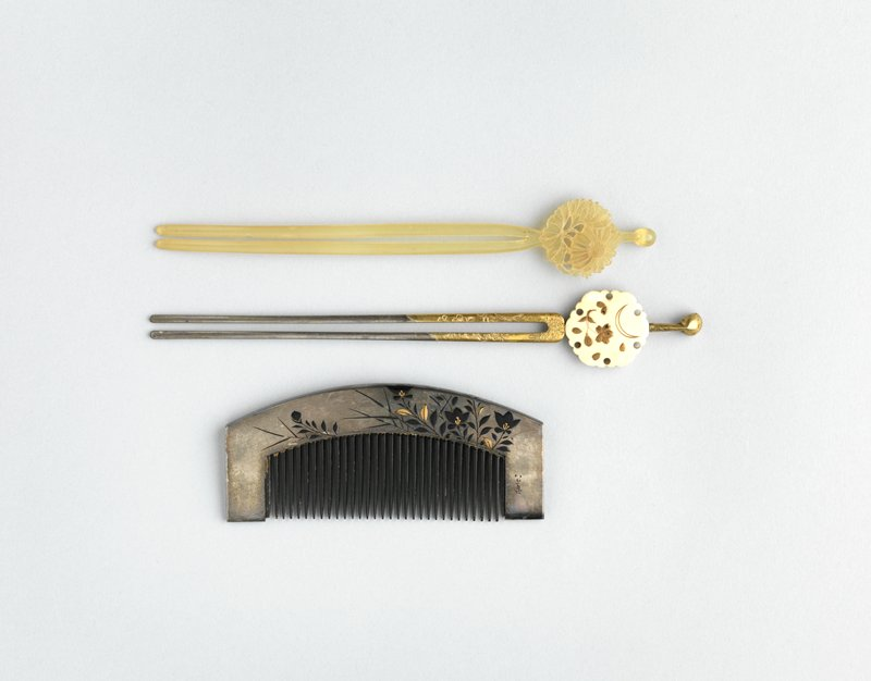 metal hairpin with white medallion featuring crescent moon and cherry blossom motif in gold; moon is outlined on one side, and filled in on other; gold foil around top of prongs with floral motif
