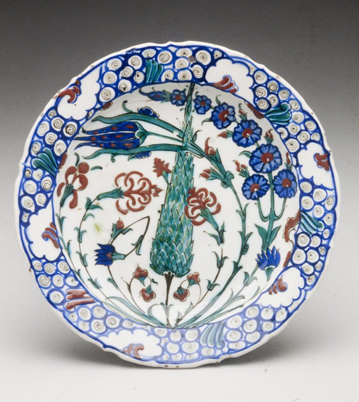 Plate fine quality white glaze; conventional floral design with pink, tulip, iris, cypress tree, etc., in blue, green and tomato red that comprise the center of the dish; band of spiral and foliage design in blue on brim; from Aynard Collection; so-called Iznik ware. Ottoman dynasty.