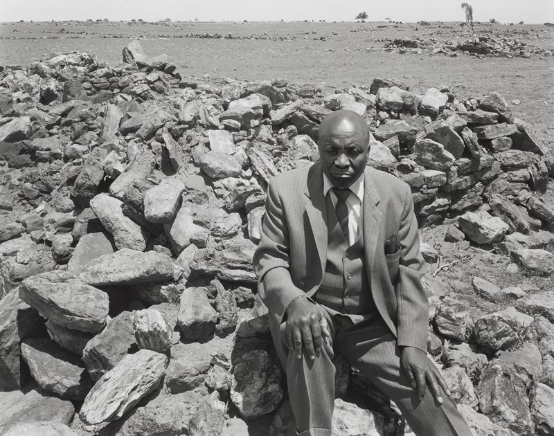 black and white photograph of a bald man in a suit seated on a pile of rubble; barren landscape