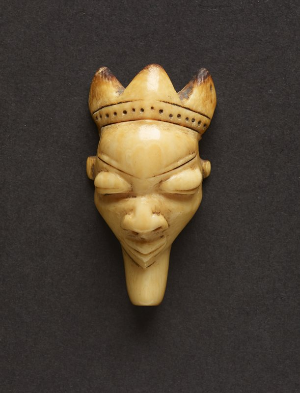small pendant of hippo ivory carved into likeness of man's face; on top of head rests three-pointed crown with a band of repeating black dots below; face has high forehead, bulging eyes, rounded nose, and mouth that protrudes to a point; man has triangular beard that tapers at bottom; piece is yellowish in hue with the reverse being a darker brown