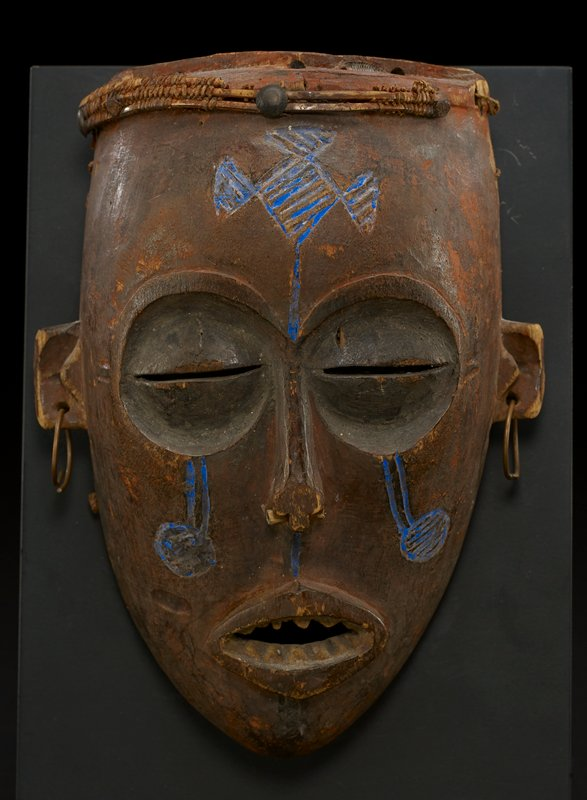 "female ""pwo"" mask; ""face"" of mask is oval and defined by two large concave eyes, with slits at center, a long thin nose with a wooden bar nose ring at its base, and a mouth that is open, revealing carved teeth (some missing); two small, square ears jut out from either side of face and each ear has a metal hoop earring; top of mask is flat with remains of decoration on its rim; blue designs are painted and carved at forehead, cheeks, and below nose; entire mask is the natural orange brown of the wood from which it was carved; however, eyes appear darker brown, and ears and moth appear somewhat lighter brown; holes line the entire edge of mask"