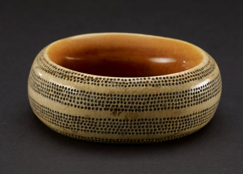 bracelet with banded decorations of silver studs; round and thick, made of ivory that appears yellow on the inside, and lighter on the outside; outside of bracelet has four stripes formed by tiny repeating studs of silver