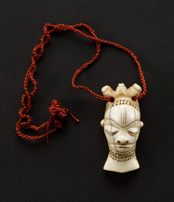 ivory amulet carved into shape of oval head, with a three-pronged headdress; eyes are large ovals and appear to be closed; a thin, uninterrupted line between the forehead and eyes reads as a brow; three vertical lines decorate the center of the forehead; nose is indicated by a small protrusion and two holes for nostrils; mouth is a dark line pointing up at center; there is a line that runs from cheek to cheek below the nose, the neck is covered with three bands of dark dots, and two holes run through the headdress and a red cord is thread through the holes; reverse of amulet is undecorated and flat; the piece is a light shade of cream, the natural color of the ivory