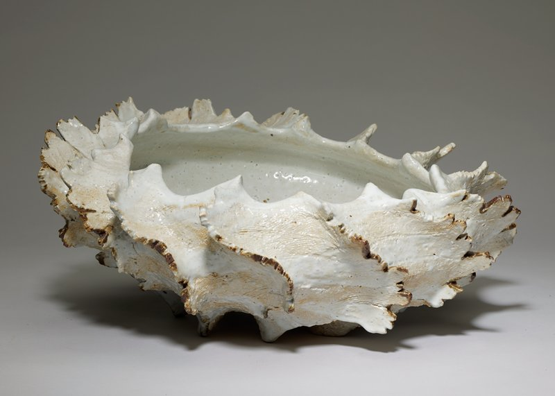 organic, shell-like form; shallow tilted bowl with scalloped rim; raised diagonal ribs on body with jagged edges; milky white glaze; tips of rib are brown; inherent bubbles in glaze throughout