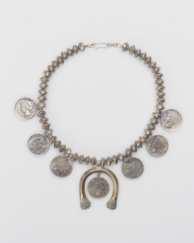 silver necklace comprised of beads constructed by fusing together two dimes, three sliver dollars interspersed on left, another three on the right, and a squash blossom pendant at bottom center encircling a seventh silver dollar