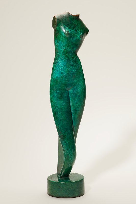 elongated vertically positioned female torso and legs to upper calf; no head, arms or feet; contrapposto pose with PR knee in front of PL; PL shoulder down; vertical tapering support on back between legs; cylindrical shaped base; green patina