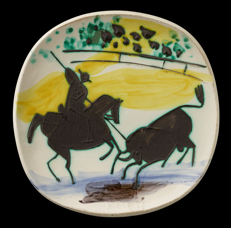 white plate with slightly squared-off shape; top surface decorated with incised and low-relief design of black silhouettes of matador on horseback at left spearing a bull at right in the head; black silhouettes of spectators at top; yellow, green and blue touches