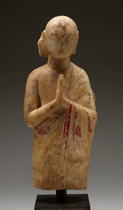 3/4 length standing figure; bald, with placid face, closed eyes, long ears with elongated lobes; head slightly bent forward; palms of hands held together at chest; figure wars a robe draped over PL shoulder and PL arm--PR shoulder, chest and arm are bare; traces of gilt, red and green pigments on garment; cream-colored stone with mottled brown areas