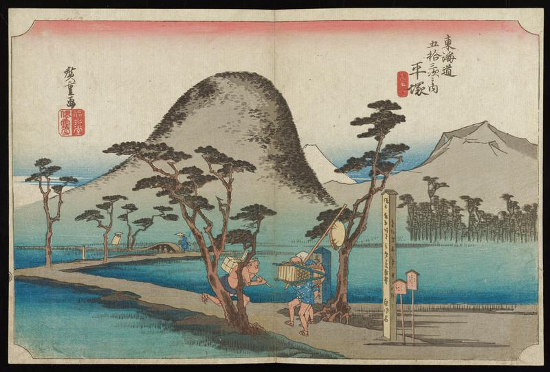winding, narrow road crossing over calm waters; two male travelers struggle with luggage near signs at mouth of road; other travelers in distance crossing bridge; a few trees; mountains in background