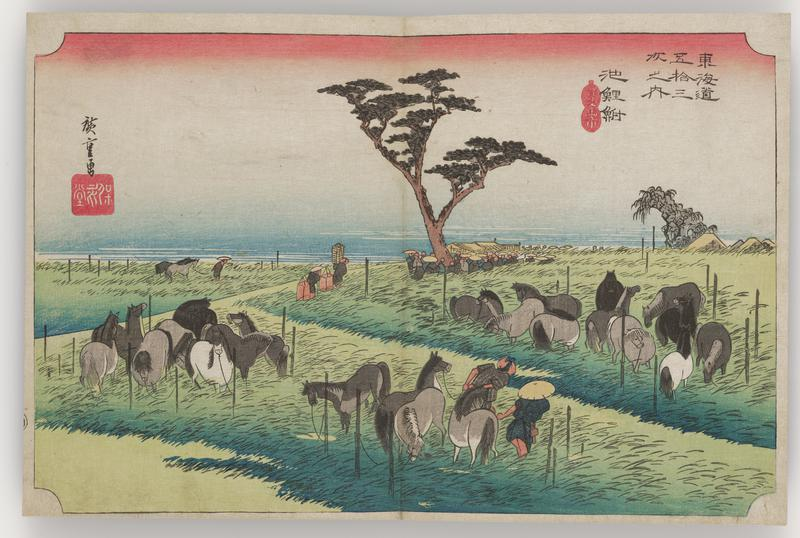 field of long grasses with a variety of horses tethered to stakes; a few people tending the horses; small complex of buildings with a larger group of people in background behind tree