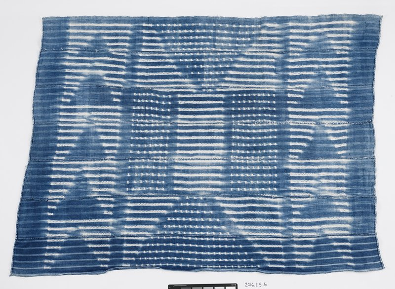 blue dyed panel with overlapping white stripes and dots that form triangle and rectangle shapes; seven strips are sewn together to form panel; two ends are stitched forming a seam
