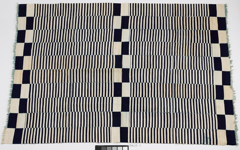 blue and white panel with fringed ends on two sides; checker pattern alternates with blue and white stripes; ten strips of fabric are stitched together for form panel
