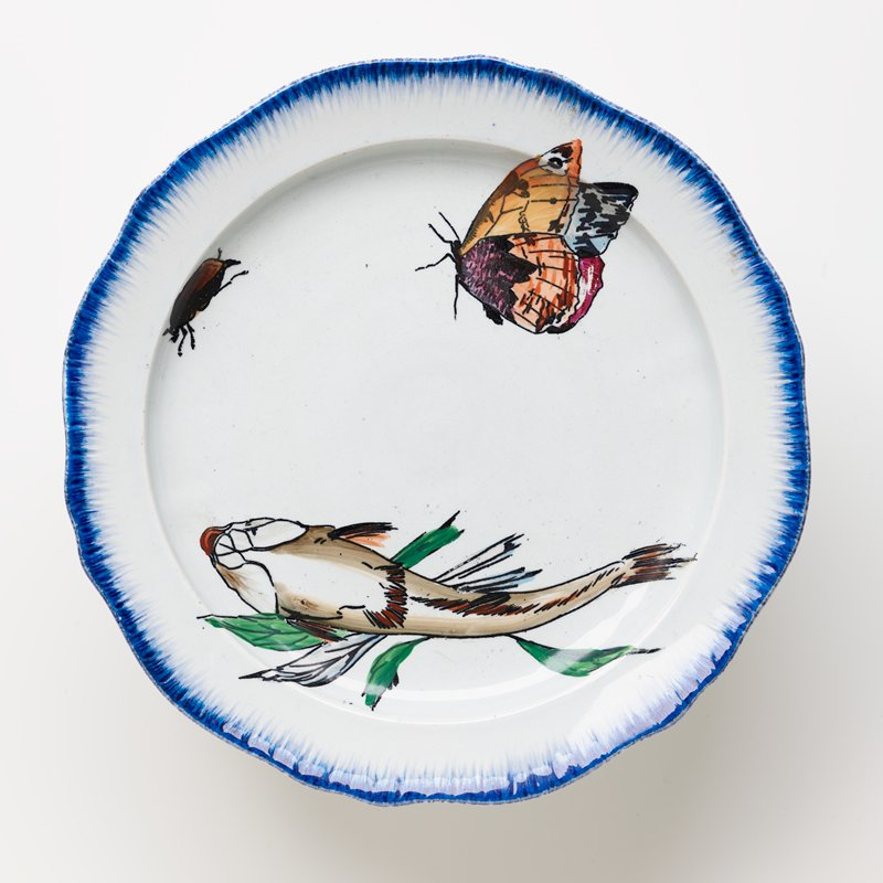 cake plate with white ground and brushed blue pigment around edge of plate and foot with painted fish seen from below, orange butterfly and a beetle on plate surface and a pink flower bud, a bee and snail on foot