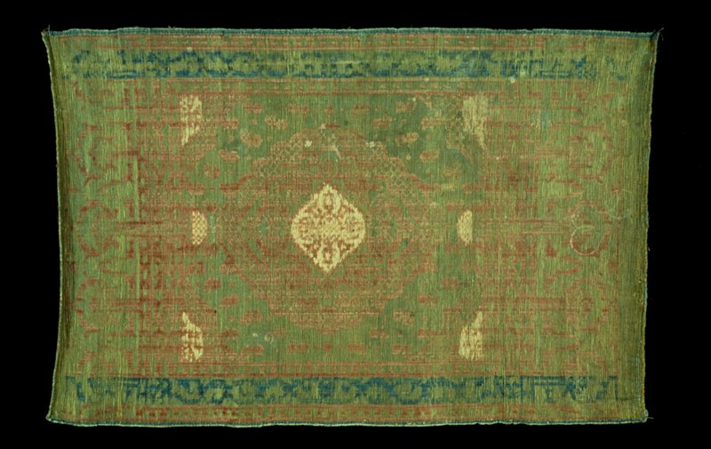 Velvet Mat green background with design in yellow thread; red pile, with border design in blue pile. Ladik.