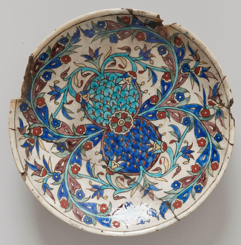dish inner base bears bold flower designs in dark and light blue, yellow, tomato red etc. on white glaze; broken
