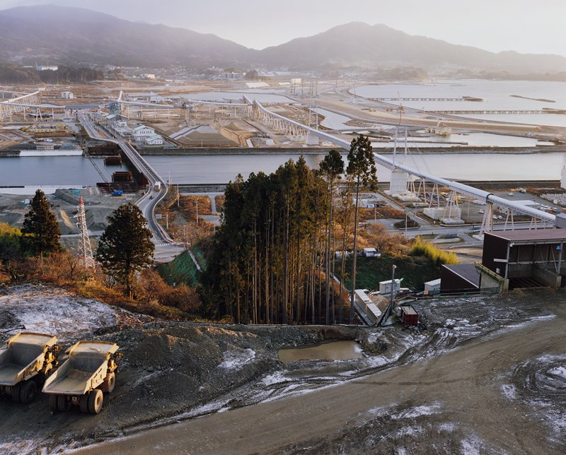 dirt roads in foreground with two dump trucks in LLC; tall pine trees at center middle ground; paved roads, water, buildings and tunnel or pipeline at right, with mountains in background