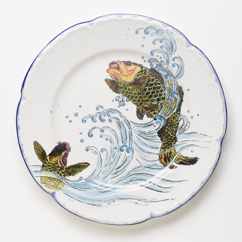 small dinner plate decorated with two jumping green fish with orange heads; blue scalloped edge