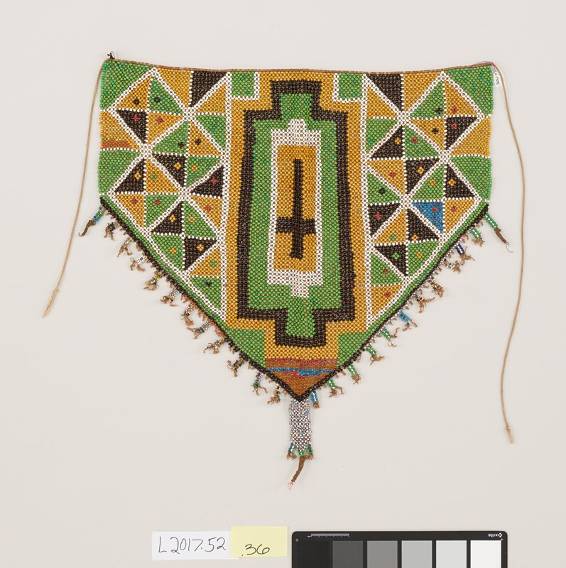 beaded apron with predominantly green, black, and yellow geometric designs; small tassels with multi-colored beads hang from bottom triangular edge; strip of multi-colored beads on bottom point of tip with four smaller woven points; strings attached on either end