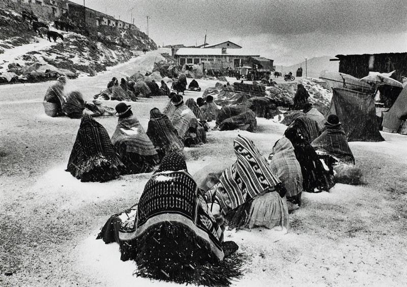 3 diagonal rows of figures, backs to camera, wrapped in blankets, seated on the ground in light snow; building with truck and motorcycle in center background