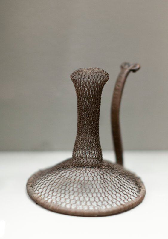hexagonal wire mesh formed into an inverted funnel shape with flaring top; wire covered frame with curving handle terminating in a pair of loops