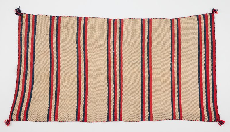 wide cream stripes with narrower blue, red and cream stripes; red and blue tassels at corners; tiny leather patch/tag at one corner