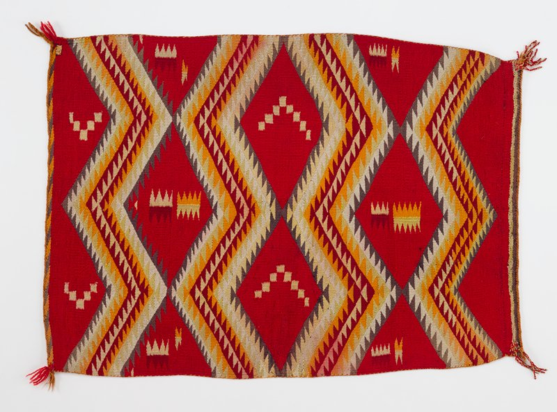 red background; zigzagging bands of gray, yellow, white, orange, and red triangles segment the red background into diamond pattern; geometric designs within diamonds; tassels at corners