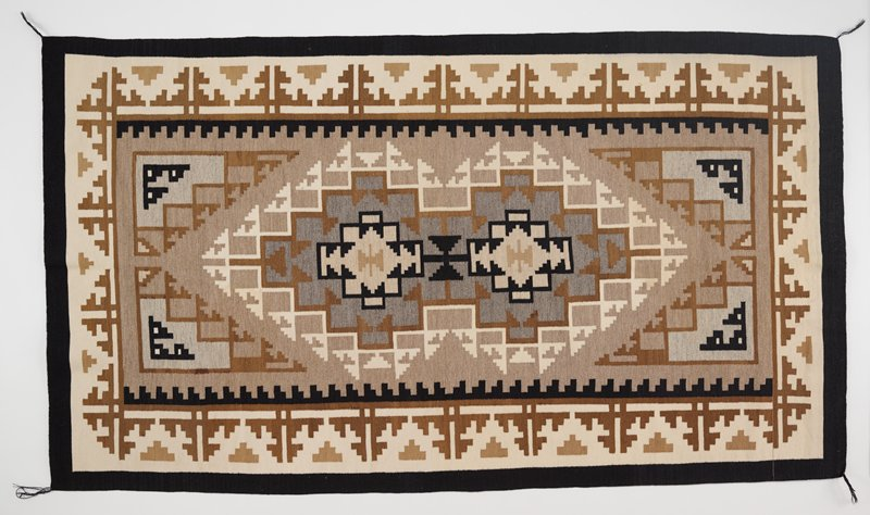 black border; intricate stepped geometric designs in shades of tan, cream and black; has a heading band