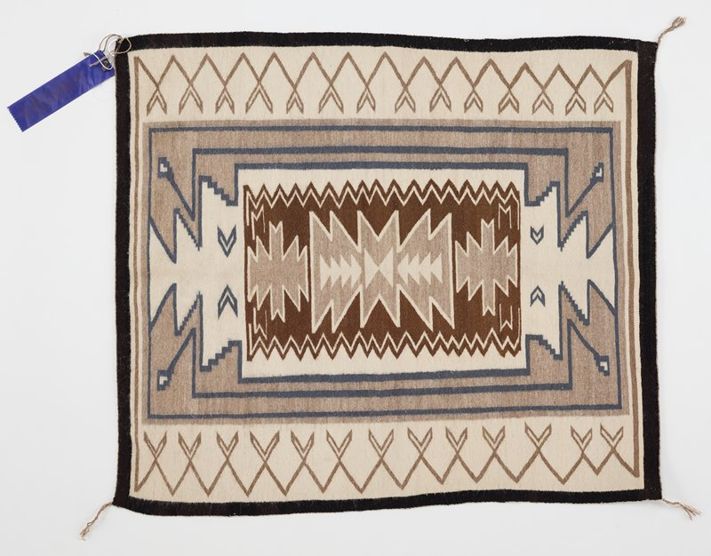rectangular textile in white, brown, wheat colors with decorative blue elements and black border; triangular geometric designs down C in white and wheat, within brown block with zigzagging edges; blue rectangular lines with zigzagging ends within wheat-colored background; thick white inner border with heart-shaped motif in wheat color; black border
