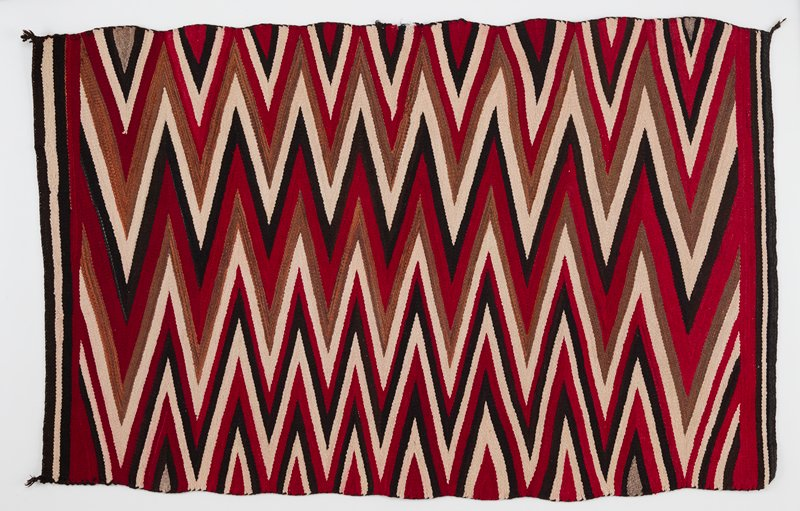 wool panel with red, brown, white and gray zig zag pattern; knotted tassels in all four corners; straight lines in gray, white and brown on the two shorter ends