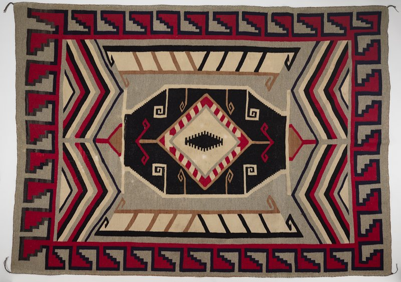 wool panel; gray background with a red and blue geometric border; blue, black, gray and cream chevron design on top and bottom; large, eight-sided shape in center with cream colored diamond in the middle with red stripes and black geometric iris shape in the center; abstract pillar shapes in brown, black and cream dye on right and left sides of center design