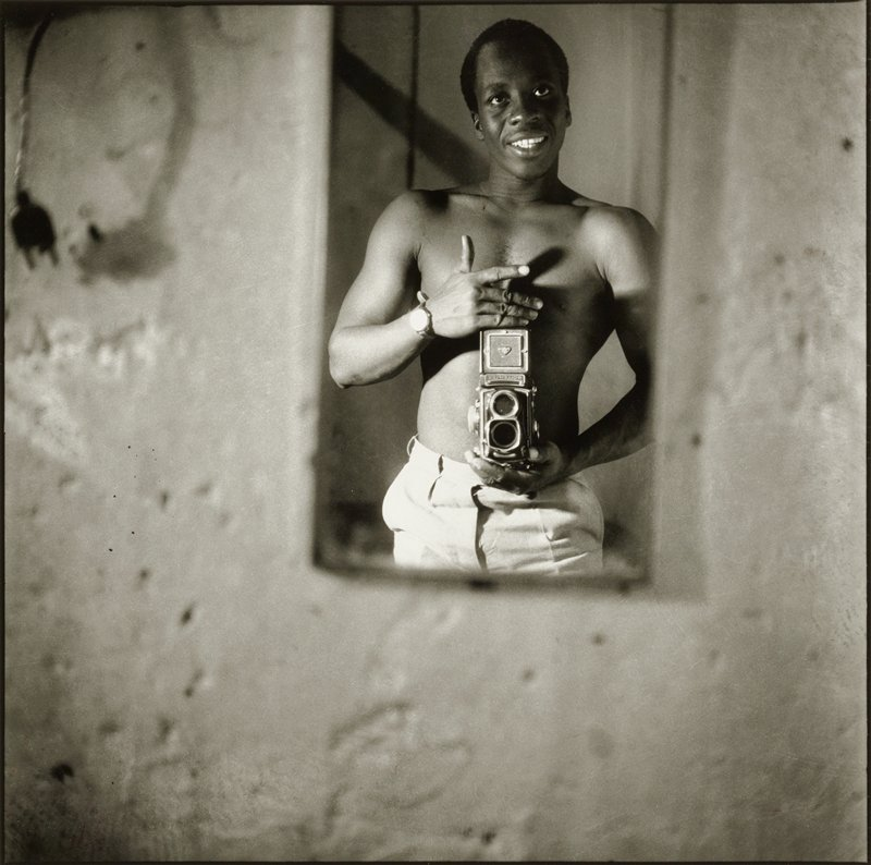 image of a shirtless smiling man holding a camera in front of his stomach, viewed in a small mirror against a concrete wall