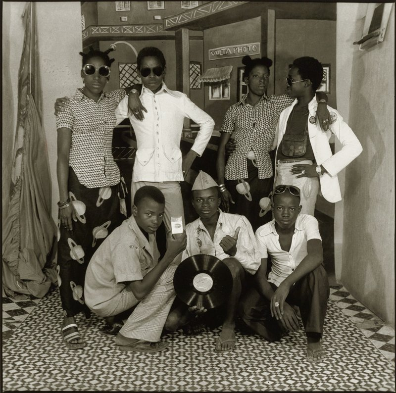 three young men crouching in foreground, with young man at left handing a pack of cigarettes and young man at center holding a record album; two young couples standing behind young men, with their arms around each other; young women are wearing blouses with the same geometric patterning (the only difference being the direction of the patterning--horizontal on girl at left, vertical on girl at right) and skirts with the same patterning of a planet with rings; girl at left wears sunglasses; painted backdrop of buildings on city street behind figures; patterned tile floor