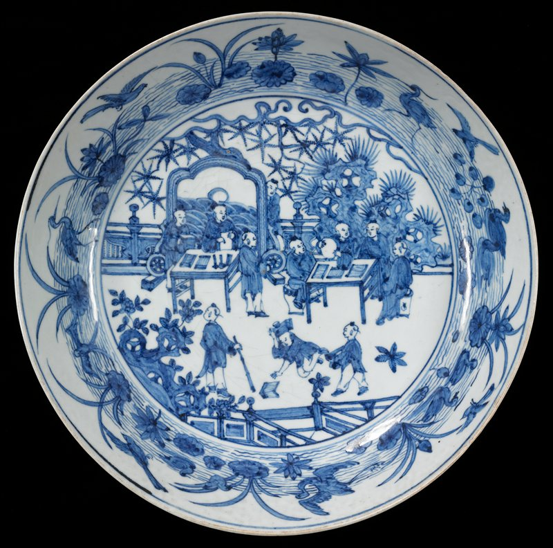 blue and white porcelain; 11 figures seated at 2 tables and standing and kneeling in front; rock in background at R; inner and outer rims decorated with water, birds and foliage
