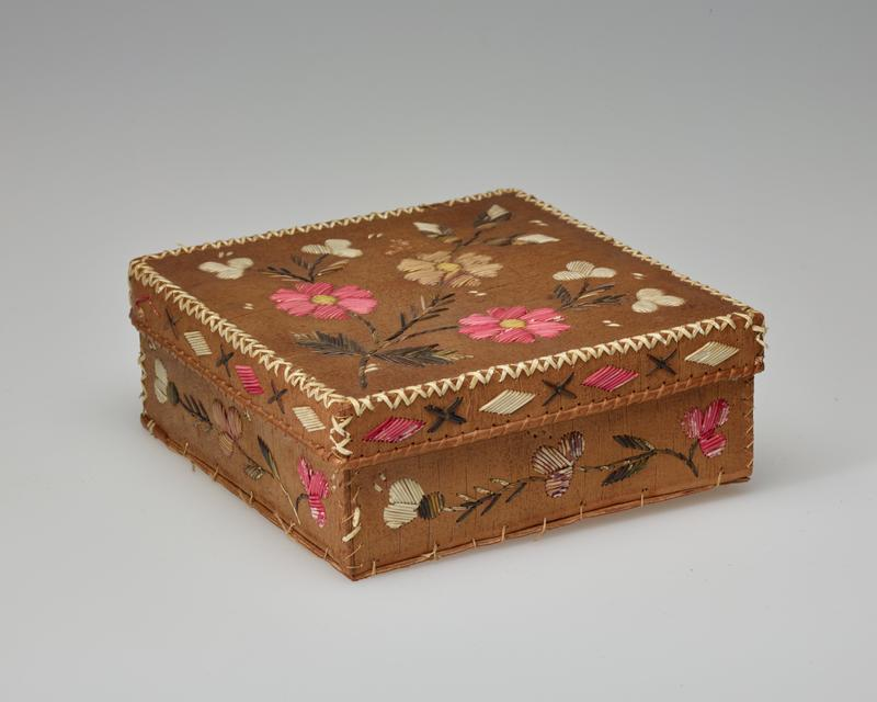 square, rather short box; cover and sides decorated with quillwork flowers in pink, yellow, white and purple with green stems and leaves; edges of cover decorated with pink and white diamonds and brown Xs