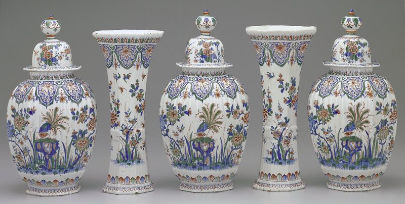 ginger jar shaped with ribbing on body and lid; lid is high dome with round finial; white ground decorated with flowers and birds near water in blue, green and orange