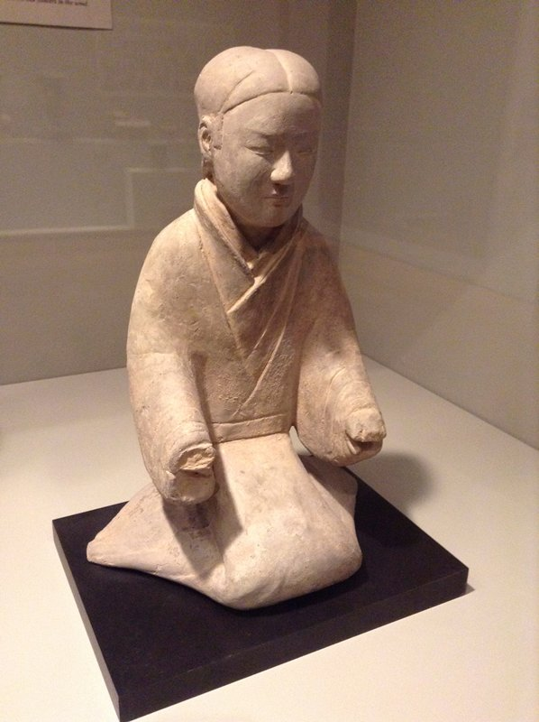 grey unglazed pottery figure of a kneeling woman looking straight ahead, wearing a robe; arms bent at elbows, straight ahead; hair pulled into low ponytail