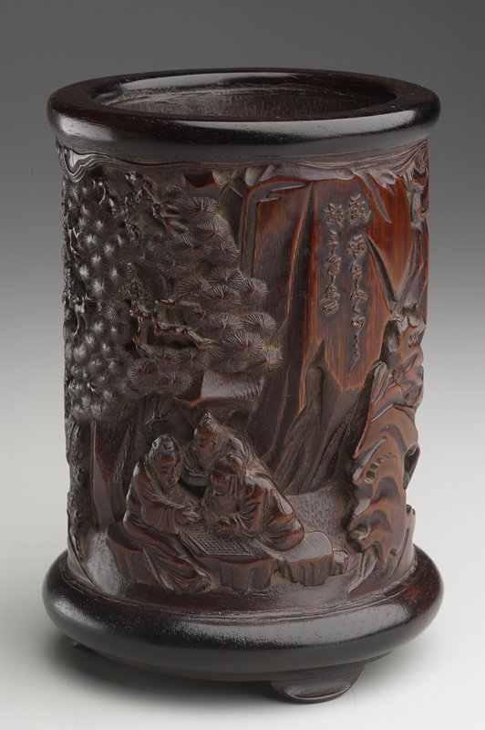 cylindrical shape with ring foot on sides at bottom and tripod feet; carved with figures in a landscape man drinking tea with attendant, man playing a stringed instrument, 3 men playing a game