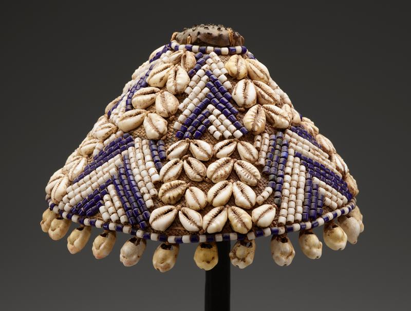 conical shape with flat top; seed pod/plant material element on top; two bands with alternating designs of columns of cowrie shells and chevrons of blue and white beads; dangling cowrie shells along bottom edge; body of beige