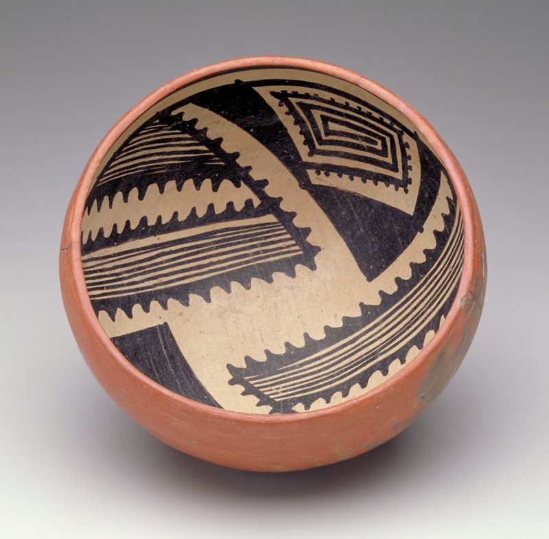bowl with rounded bottom; red on exterior; interior decorated with 4 black triangles, filled with geometric patterns, on a white ground